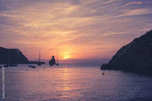 Quiet scene: Sailboats in a harbor at sunset. Mediterranean sea of Ibiza island
