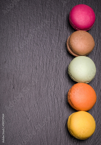 Top view of colorful macarons on dark background Poster