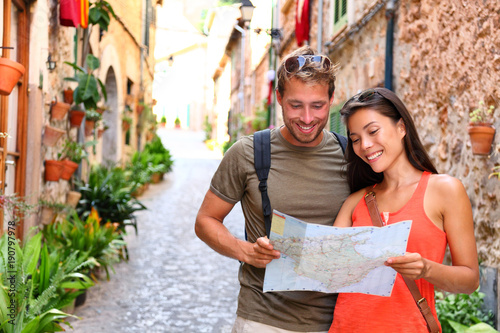 Leinwanddruck Bild Europe travel tourists couple looking at map to find directions walking in old streets of spanish city Palma in Mallorca, Spain. Asian woman, Caucasian man on Cruise vacation during summer holidays.