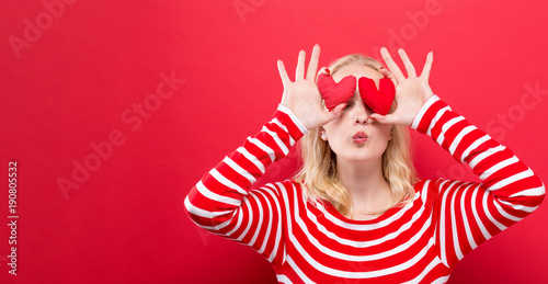 Happy young woman holding heart cushions on a solid background