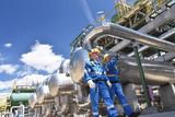 Arbeiter in einer Raffinerie - im Hintergrund Anlage zur Produktion von Treibstoff aus Erdöl - Industrieanlage mit Rohrleitungen // Workers in a refinery - industrial plant with pipelines