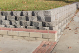 Residential retaining wall featuring a variety of stacked blocks and mortared brick textures, horizontal aspect - 190811360