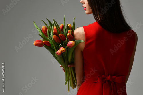 Beautiful woman with bouquet of tulip flowers in red dress and little sticker on tulips