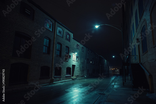 Dark urban city alley at night after a rain featuring vintage warehouses.