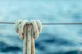 The rope knot on a steel cable on background of ocean. - 190837922