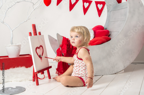 Valentine's day - portrait of a cute little baby girl in a decorated holiday studio of the Valentine's day .