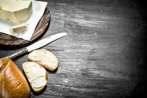 Wall mural Butter with a knife on the board.