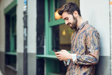 Young man wearing casual clothes looking at his smartphone in the street. - 190849795