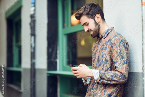 Young man wearing casual clothes looking at his smartphone in the street.