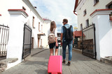 Two travelers on vacation walking around the city with luggage. - 190849937