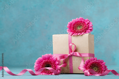 Pink flowers and gift box with ribbon on turquoise table. Greeting card for Birthday, Woman or Mothers Day.