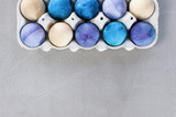 Background with blue and violet easter eggs in the box on the textured gray table - 190855979