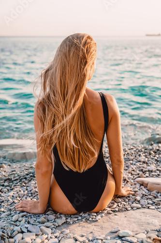 Young woman in bikini swimwear sit on beach and sea with warm sunset colors.
