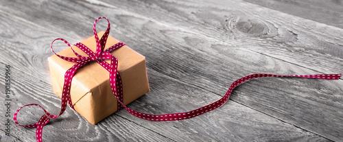 Leinwandbild Motiv Paket mit roter Schleife auf rustikalem Holz  --  Hintergrund, Banner