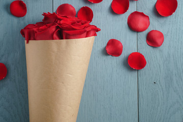 red roses bouquet on blue wood table top view