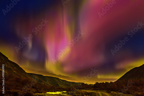 Foto op Canvas Crimson Northern Lights. Northern lights in the mountains.