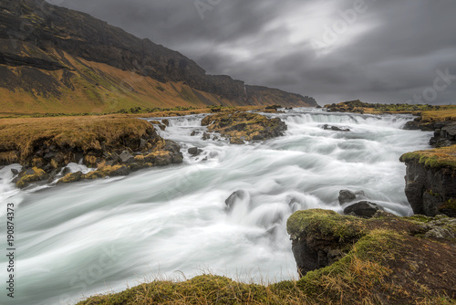 Slow motion capture of waterfall flowing near mountain slope, iceland
