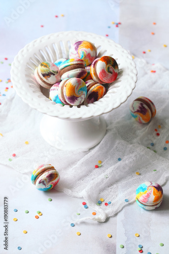 Foto op Aluminium Macarons Rainbow Macarons with Milk Chocolate Filling in vase, on light blue background.