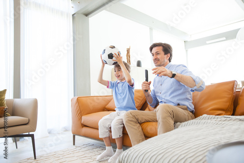 Boy watching soccer match with father
