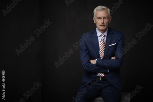 Confident businessman portrait. Executive senior lawyer businessman wearing suit and looking at camera while standing at isolated black background with copy space.