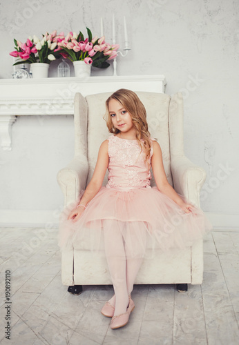 cute little girl in a dress sits in an armchair