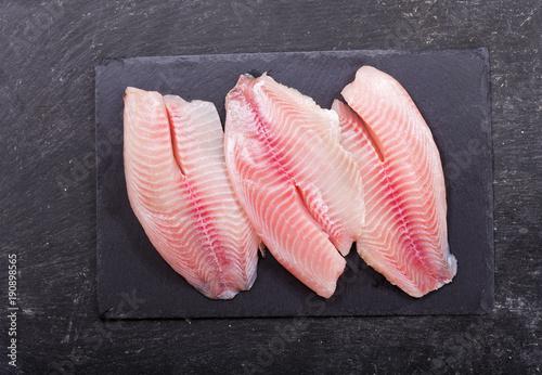 fresh fish fillet on dark board