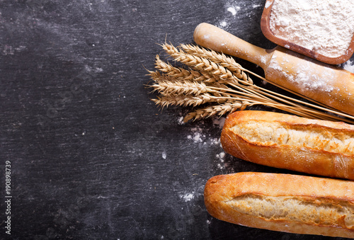 bread with wheat ears and bowl of flour, top view