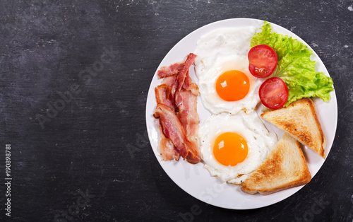 plate of fried eggs with bacon and vegetables