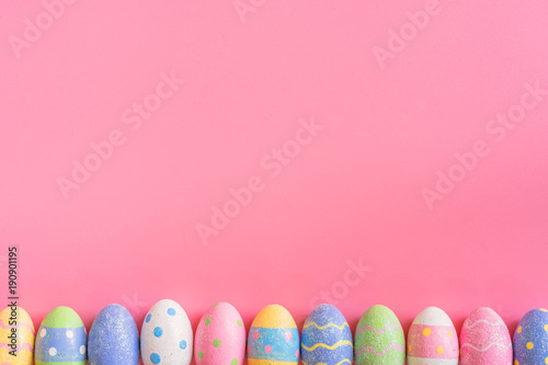 Colorful easter eggs on pink pastel color background with space.