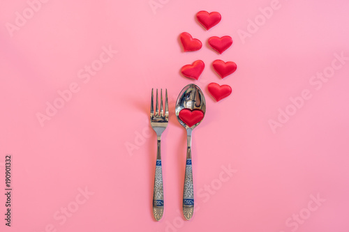 Cutlery set and red heart on pink pastel color with space for text.