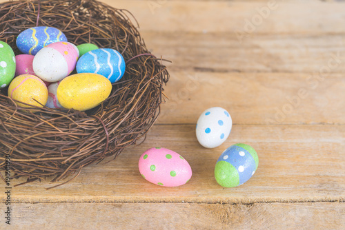 Colorful easter eggs in neat on plank wooden background with space.