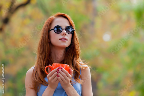 Young redhead woman with cup of tea