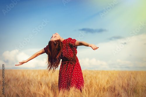 Young redhead girl with open hands standing at wheat field