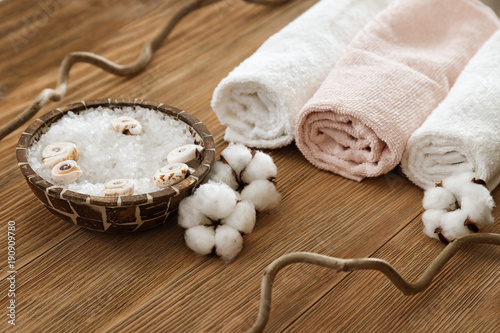Foto op Plexiglas Spa White sea salt in bowl and soft fluffy towel on wooden textured surface. Spa composition. Sea salt for bath.