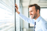Businessman looking though the window at modern office - 190914572