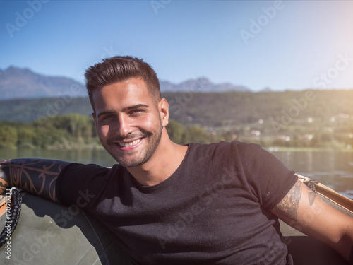 Aluminium Zeilen Portrait of young bearded handsome man with tattooed body looking sexually at camera sailing in boat.