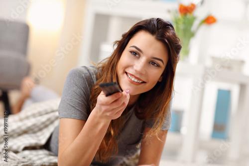 Beautiful young woman relaxing at home watching tv
