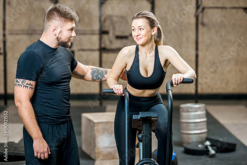 Young woman training on the air exercise bicycle with handsome trainer in the gym