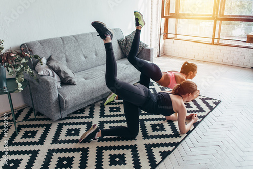 Two sportive female friends doing butt toning exercise performing donkey kicks at home