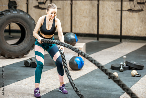 Sticker Athletic and beautiful woman swinging with a big rope training in the gym