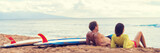 Couple surfers relaxing after surfing on hawaiian beach. Two people lying down on sand beach at sunset next to surfboards after a surf class in Hawaii, panorama banner crop. - 190926154