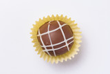 Homemade chocolate truffle.  Flat lay of candy ball on white table.