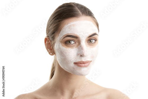 Zobacz obraz Beauty young female in facial treatment. Close-up shot of a woman with a mask applied to her face. Isolated on white background.