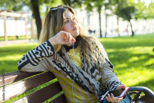 Fotobehang Muziek Technology smartphone nature outdoor concept. Girl listening to music. Young lady in park sitting on bench enjoying sound wearing headphones.