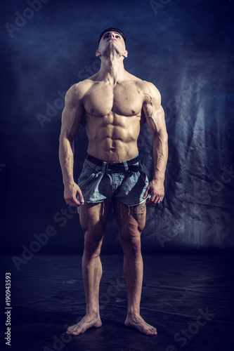 Good Looking Young Gym Fit Man Showing His Sexy Six Pack Abs While Looking Up, on Dark Background.