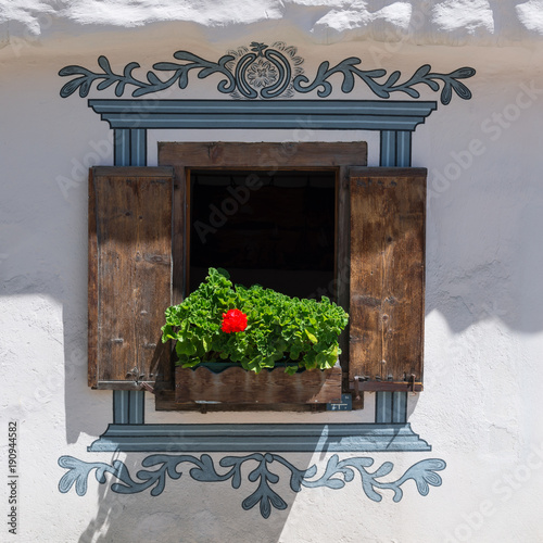 Window on a white wall. Vintage. Decoratively painted window on the wall of the house. Flower on the windowsill. Wooden shutters. Vintage houses in the canton of Graubunden.