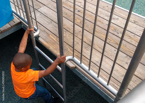 Poster Chicago A young black boy climbing the playground ladder