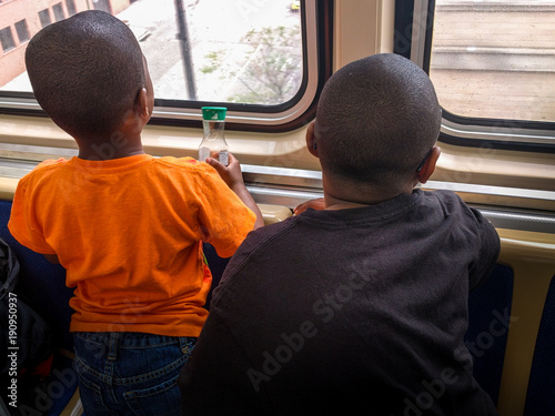 Poster Chicago Two black boys looking out of the window on an elevated train.