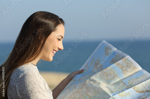 Tourist reading a map on the beach