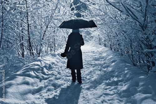 Young woman walks with umbrella.